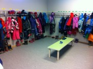 The outdoor gear room filled with rain/snow suits and runner boots.
